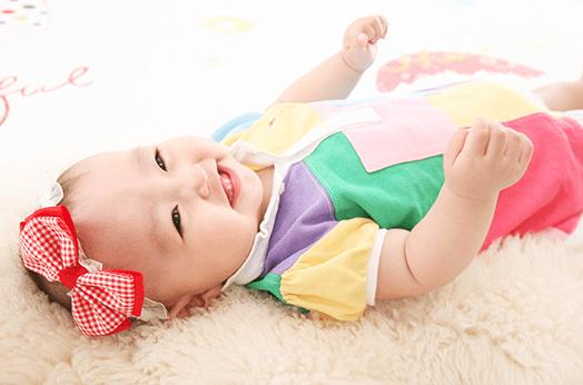 赤いリボンをした赤ちゃんが床に寝転んで笑っている写真