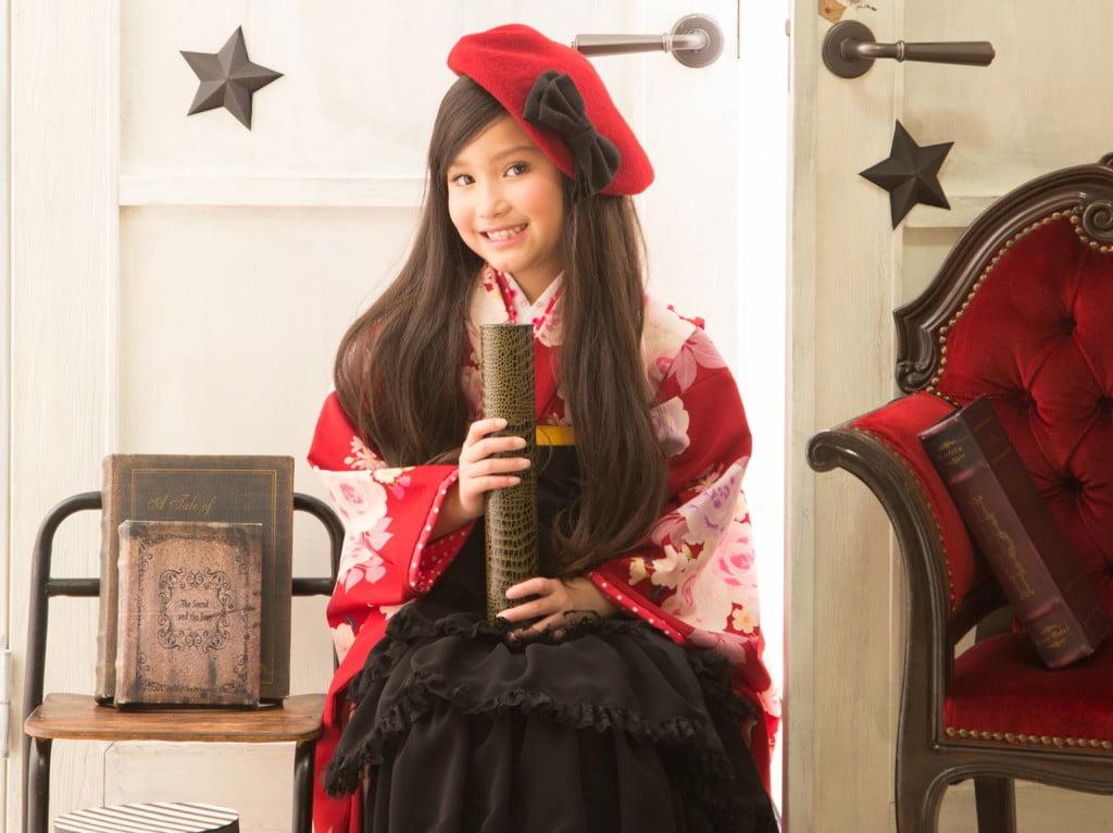 赤い着物に黒い袴と黒いリボンが付いた赤いベレー帽でコーディネートした女の子の卒業袴写真