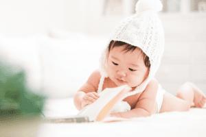 柔らかい白色のニット帽と背景が爽やかな本を読む赤ちゃんの百日写真