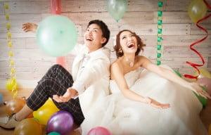 座っている新郎新婦にたくさんの風船がふわふわしている結婚写真