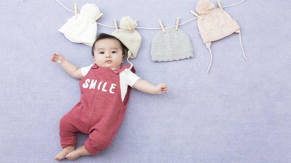 可愛い四つのニット帽と「SMILE」ロゴの入った赤いつなぎを着た赤ちゃんの百日写真