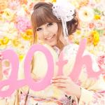 色とりどりの可愛いお花の背景で20thの飾りを持った振袖を着た女性の成人写真