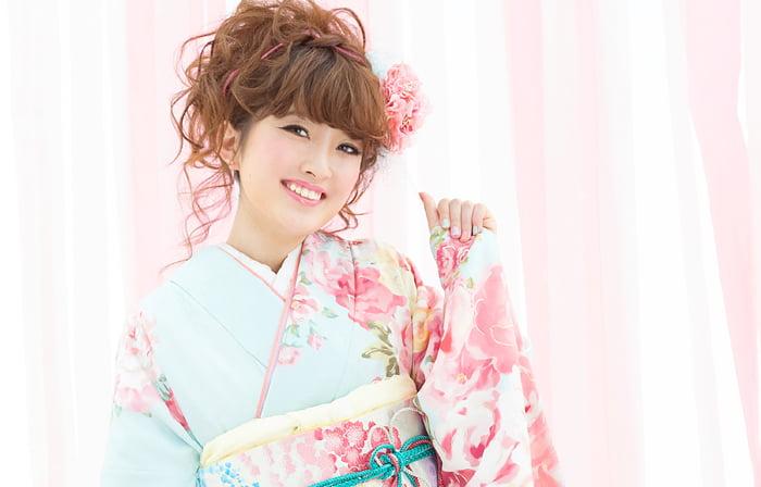 ふんわりしたピンクの背景で水色の振袖を着た女の子の可愛らしい成人写真