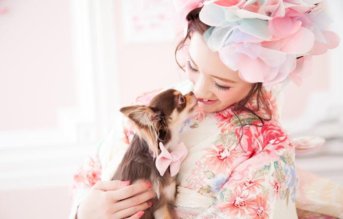 ペットの犬を抱いて頭に大きなお花の髪飾りをのせた女の子の成人写真