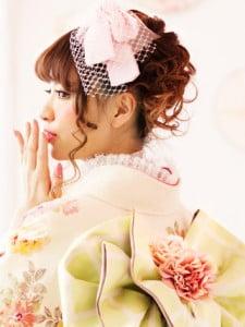 ピンクの着物に大きなリボンを合わせたロマンティックなアップスタイルの写真