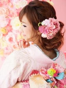 ピンクの着物にピンクのお花の髪飾りを合わせたふんわりゆるい編み込みスタイルの写真