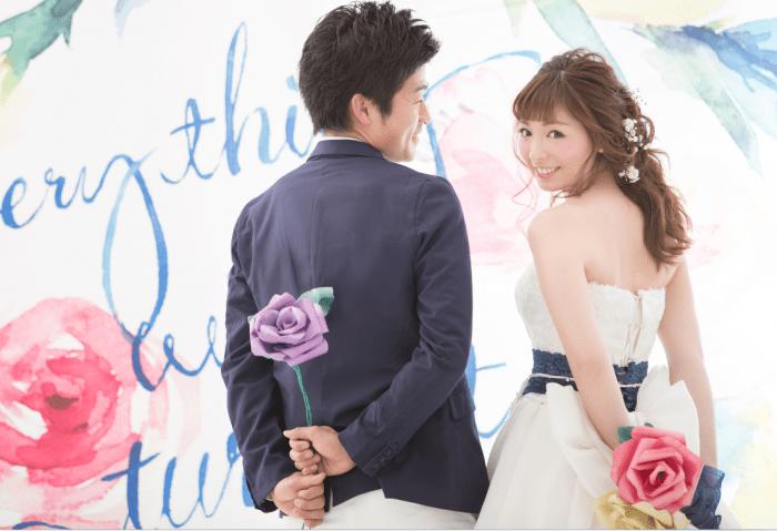 ネイビーとホワイトの衣装が爽やかな新郎新婦が後ろ手に大きなバラの花を持って微笑んでいる写真