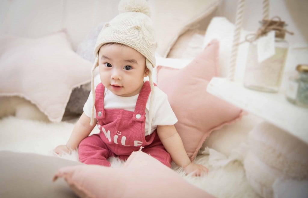 星型のクッションに囲まれてニット帽が可愛い、赤いつなぎを着た赤ちゃんの百日写真