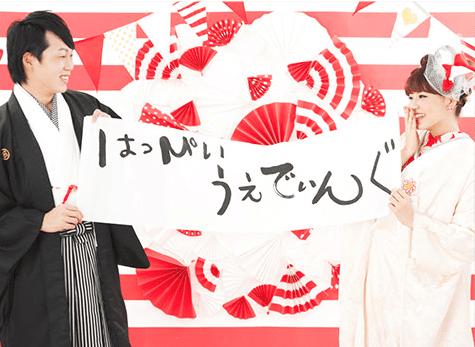 はっぴいうぇでぃんぐと書かれた習字の紙を持った和装の新郎新婦の結婚写真