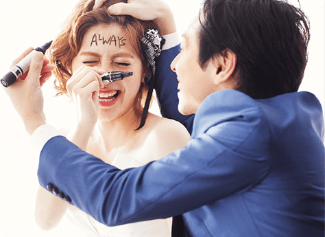 お互いのおでこにマジックで文字を書き合う新郎新婦の結婚写真