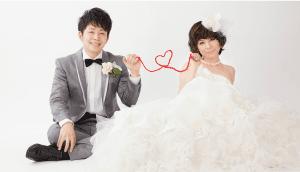 タキシードを着た新郎とウェディングドレスの新婦がハート形の赤い糸で結ばれている結婚写真