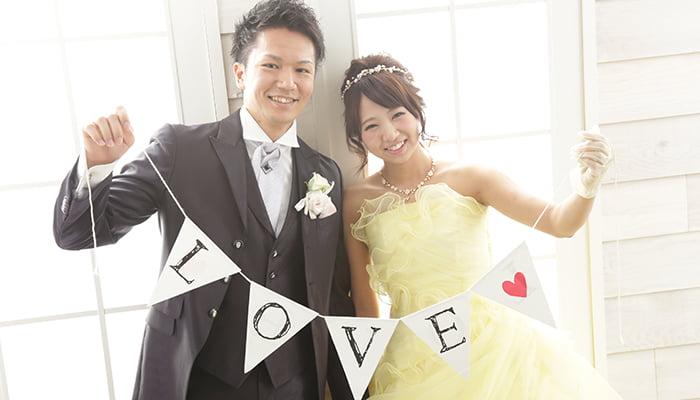 窓際で、LOVEの文字が入ったフラッグを持ったタキシード姿の新郎と黄色のカラードレスを着た新婦の結婚写真