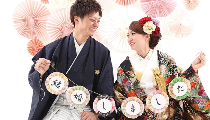 結婚しましたの文字が入った和風のガーランドを持った、和装の新郎新婦の結婚写真